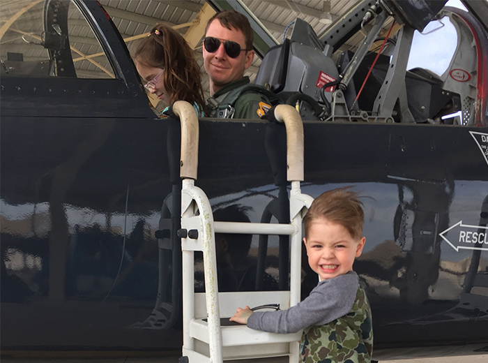 A man sits in the cockpit of a T-38 aircraft. His daughter sits next to him and his son climbs the ladder to the cockpit.