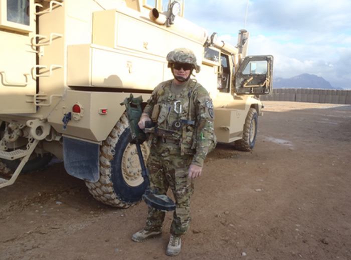 A man in military gear stands in front of a large truck.
