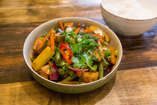 Bio-Tofu in Würfeln, gebraten mit Möhren, Zwiebeln, braunen Champignons, Shiitake-Tamarinde-Sauce und Kräuter. Veganes Gericht aus Vietnam: Đậu Hũ Sốt Me