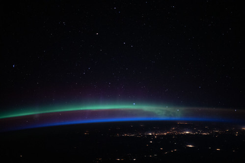 An aurora above the city lights and a beneath a starry sky | by NASA Johnson