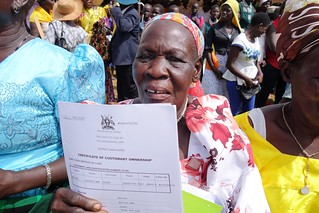 A woman shows her certificate of customary ownership