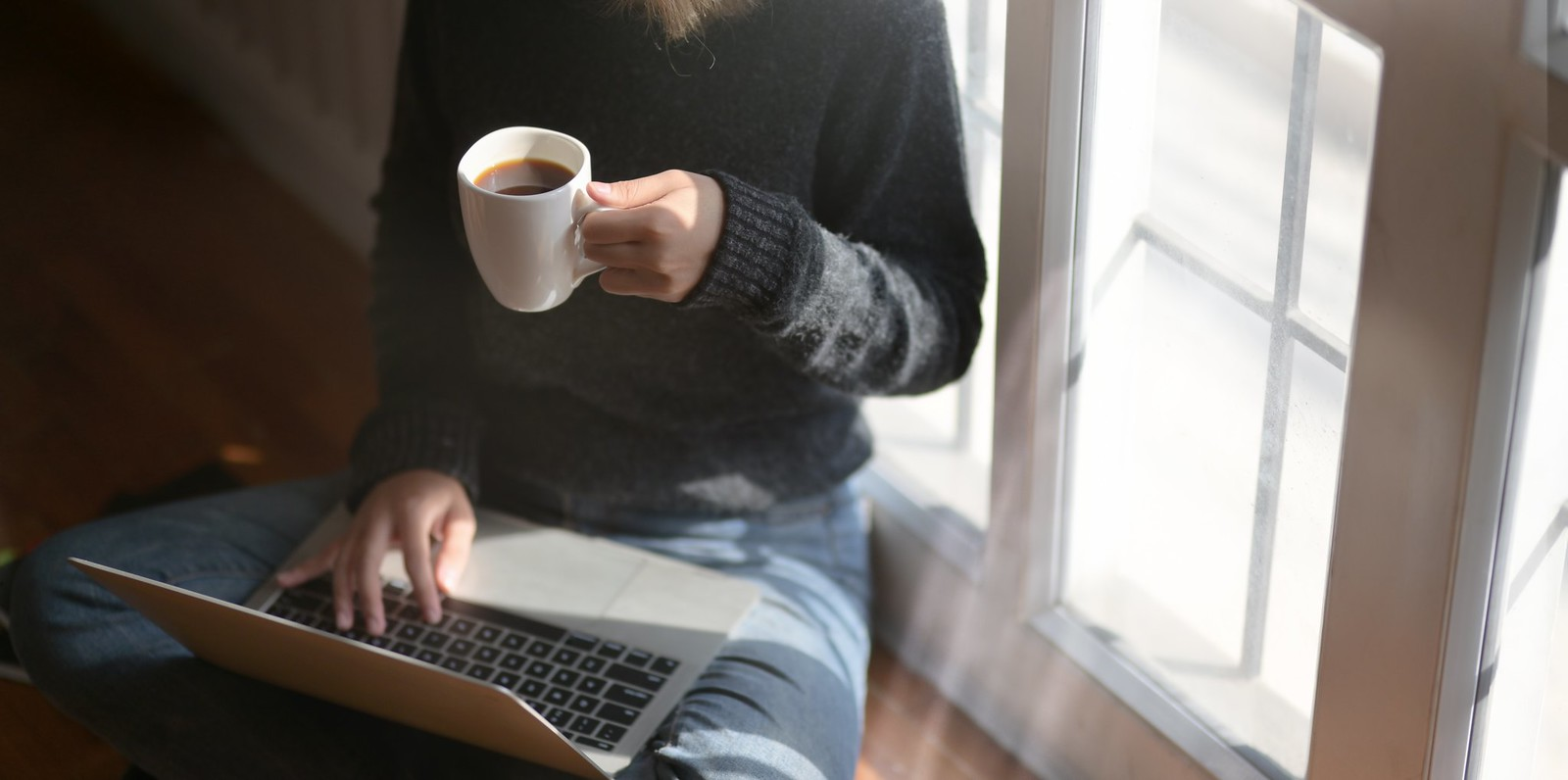 Woman using laptop while holding a cup of coffee - Credit to https://homegets.com/