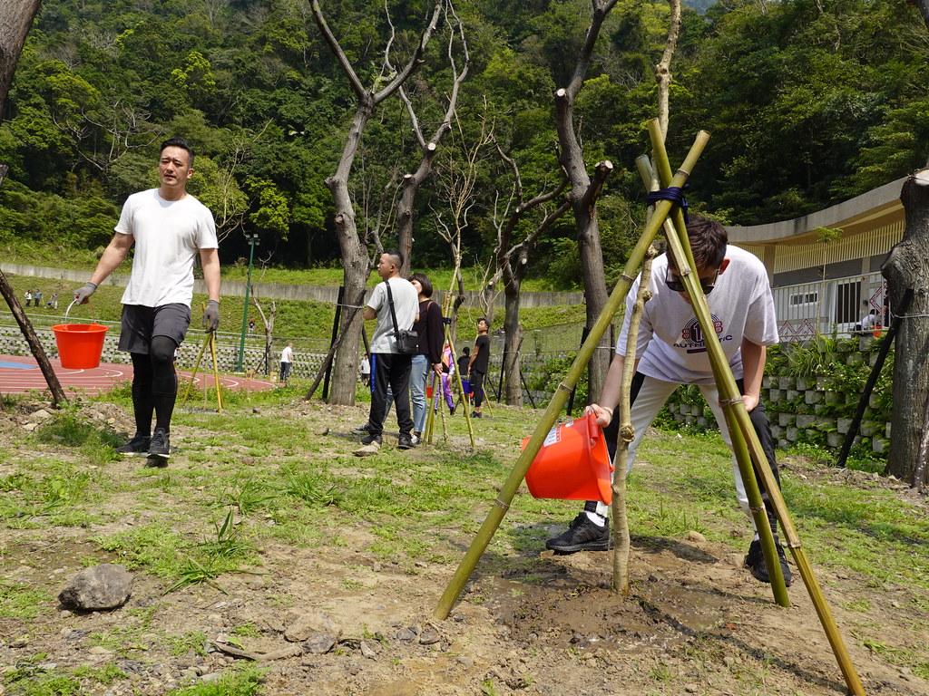 把樹埋入土壤中固定好以後,民眾替自己的樹苗澆灌第一次的水。孫文臨攝