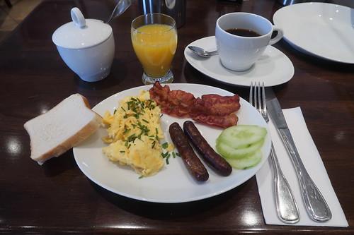 Toast zu Rührei mit gebratenem Frühstücksspeck und kleinen Würstchen