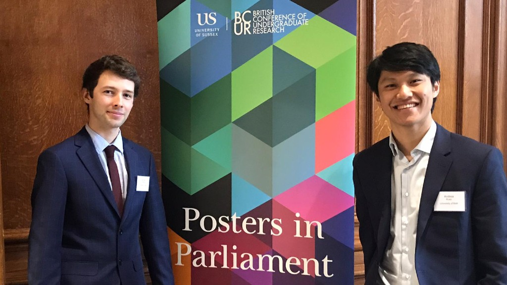 Two students from the University standing in front of a banner in the UK Parliament.