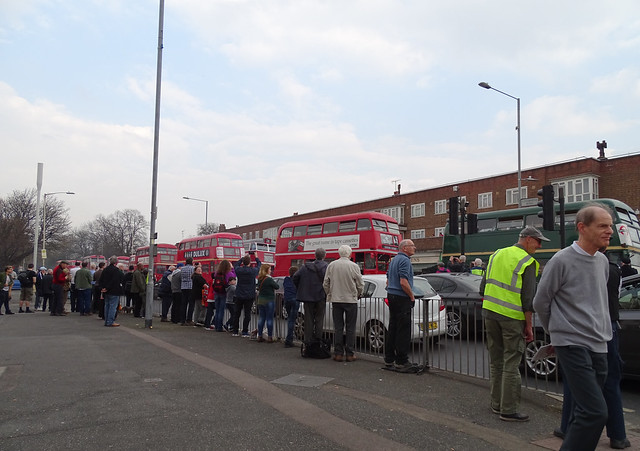 PEOPLE STANDING AT A STREET SAFETY BARRIER AS BUSES PASS BY ON THE ROAD AT A RT BUS FESTIVAL IN AN EAST LONDON BOROUGH SUBURB STREET EVENT ENGLAND DSC01752