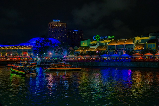 Clarke Quay with tourist bum boats at night by the Singapore river