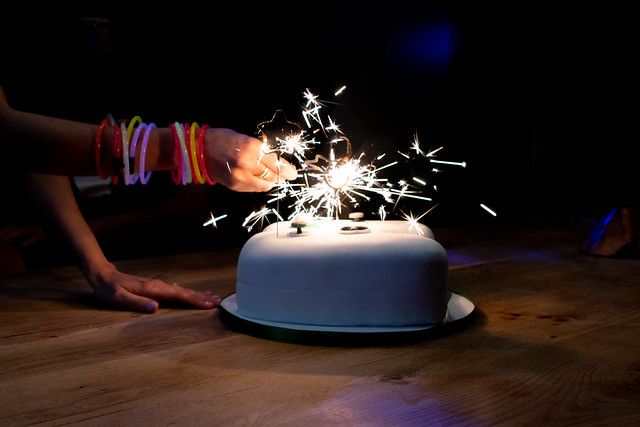 Hand Lighting Candles on a Birthday Cake