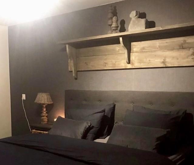 Houten regaal boven bed sobere slaapkamer