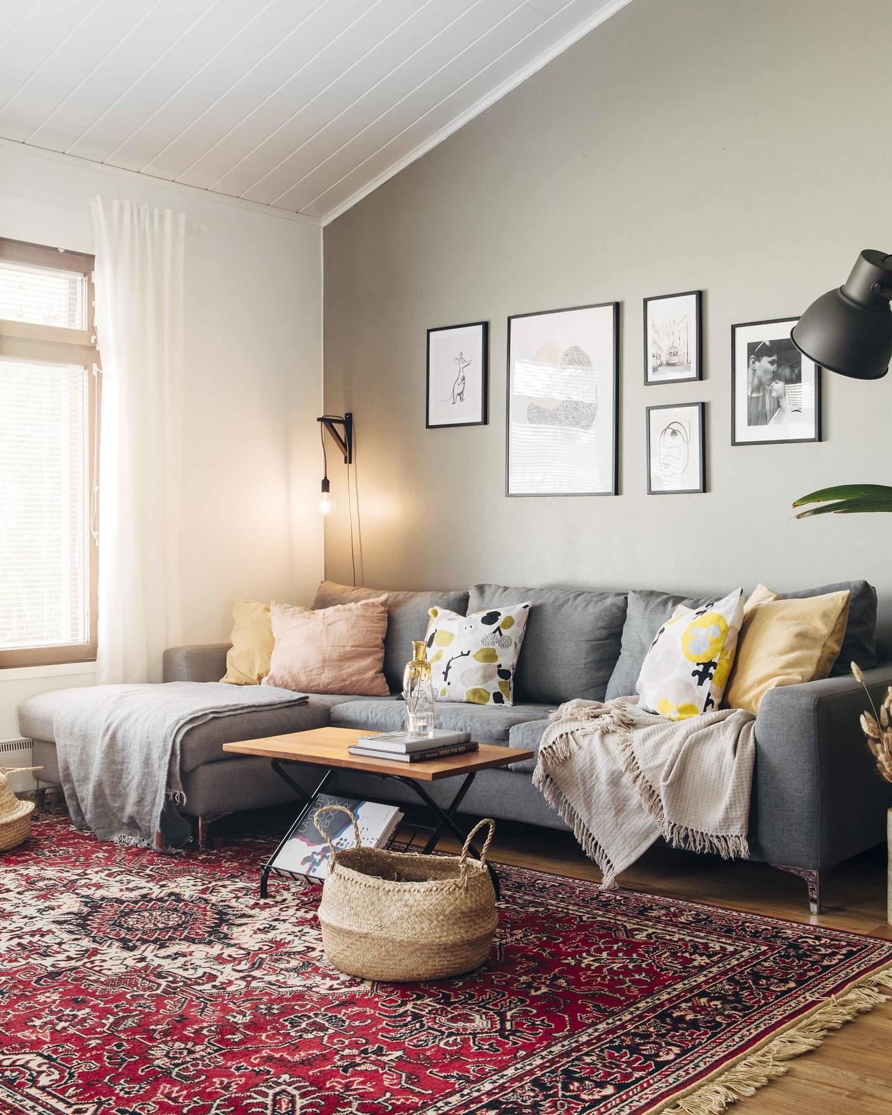Boheemi olohuone, jossa on punainen persialainen matto ja harmaa sohva.