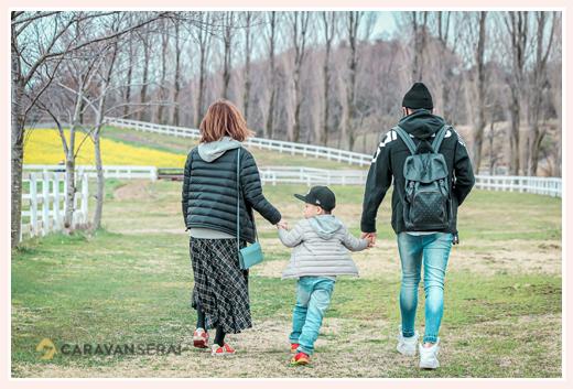 牧場を歩く親子3人の後ろ姿