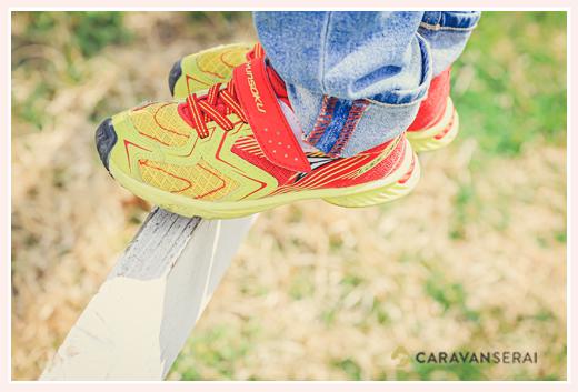 男の子の足元のアップ写真 オレンジと黄色のスニーカー