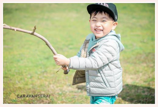 長い枝を見つけ手にして喜ぶ男の子