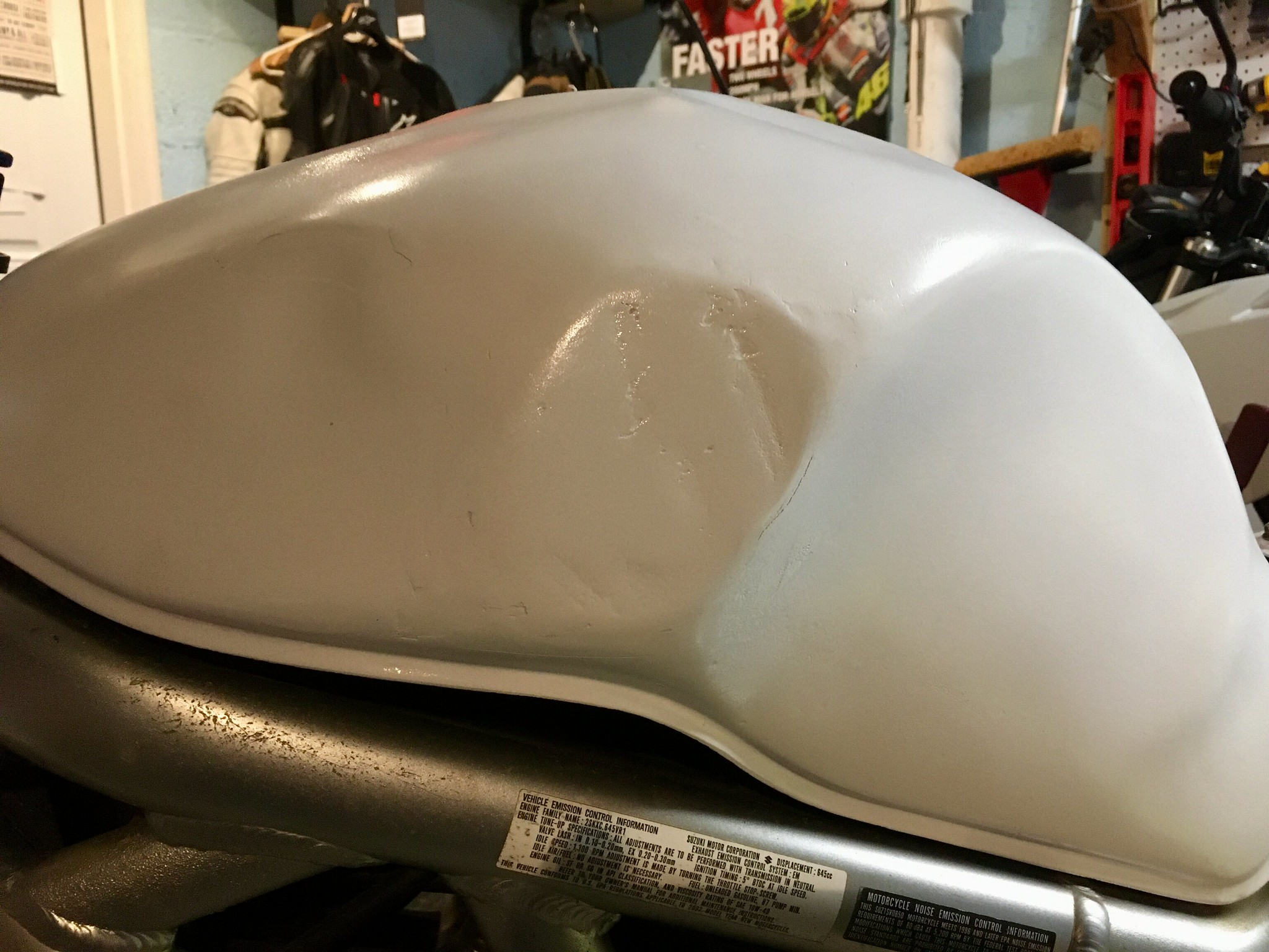 Dented motorcycle task repaired with Bondo