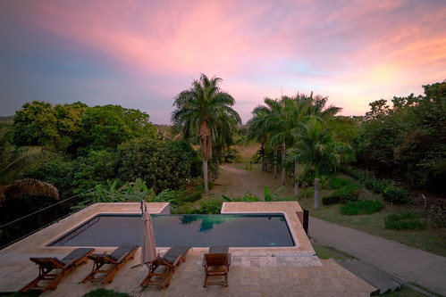 gloaming deck loungers pacific outdoors sunset sky colour pink orange tropics palm pool view vista ultrawide sony nex7 sel1018 costarica nicoya playa nature green light water sun clouds landscape
