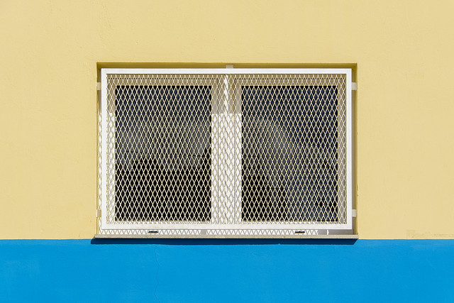 White window in a yellow and blue wall
