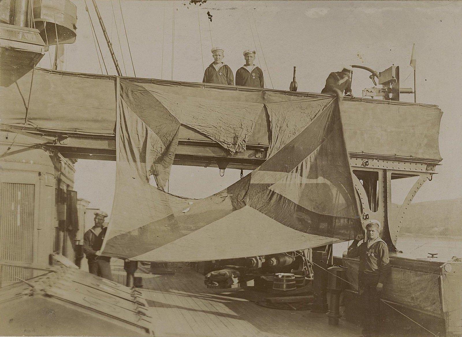 Матросы растягивают порванный флаг над палубой корабля. 1905 г.