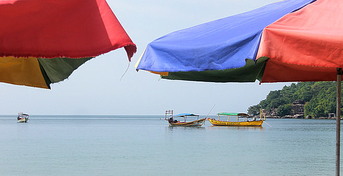 Umbrellas framing a vista of boats at Sihanoukville in Cambodia