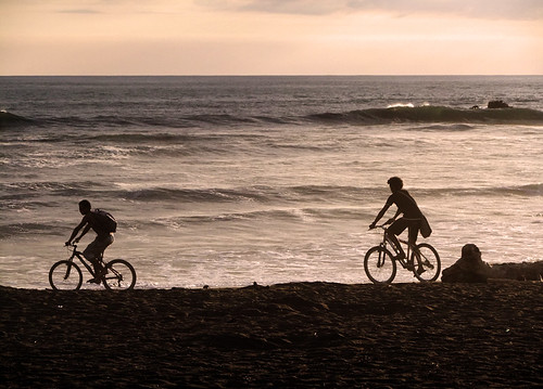 Bikes on the beach silhouetted against the late afternoon light in Ostional, Costa Rica