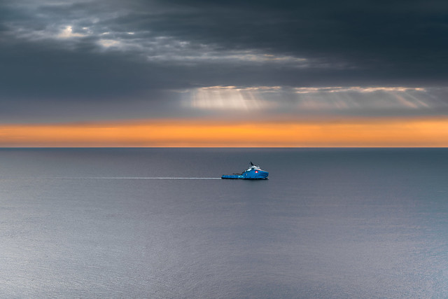 A ship gliding across the smooth surface of the Atlantic under the golden dawn. I took this photo at Cape Spear. I like the calm atmosphere in this photo.