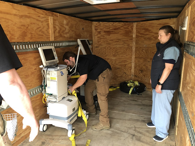 Three people place a ventilator in a transportation truck