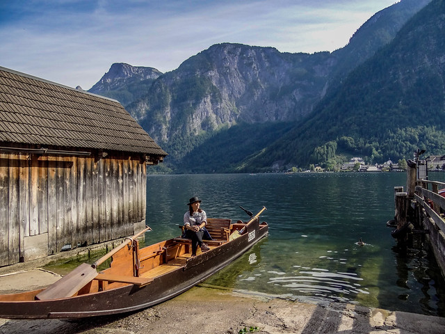 A lady tourist posing on a boat with the majestic background of Lake Hallstatt in Salzkammergut. Austria.