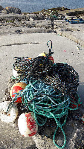 A pile of fishing nets tied with turquoise ropes on a rocky beach on the Aran Island of Inisheer in Ireland