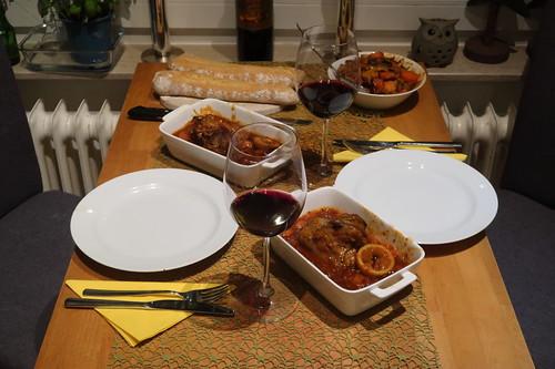 Lammhaxen in Tomatensoße mit frisch gebackenem Baguette und mediterranem Gemüse (Tischbild)