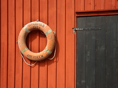 Lifebuoy on the wall of a red boathouse with a black door in Gronemad, Sweden