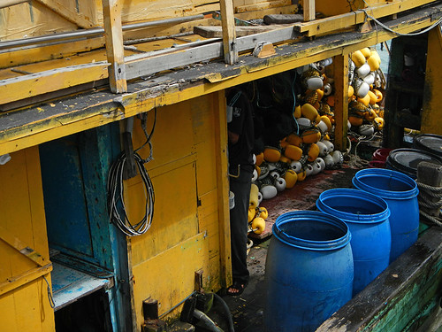 Yellow fishing boat with blue barrels and a pile of yellow buoys at a dock in Pangkor, Malaysia