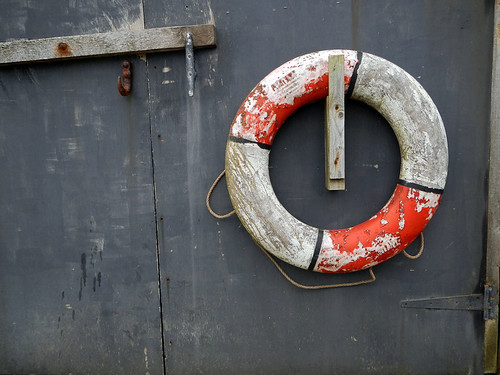 Weathered lifebuoy on a wall in the harbour of Porthgain in Wales