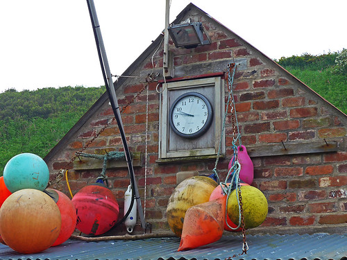 House decorated with colourful buoys in the harbour of Porthgain in Wales