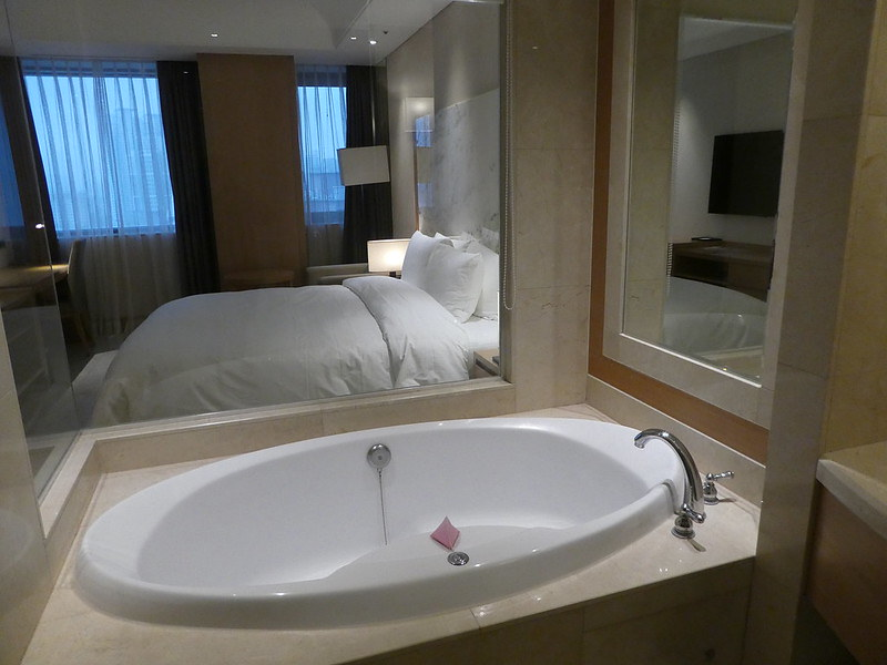 Jacuzzi bath with glass wall opening into the bedroom, Arban Hotel, Busan, South Korea