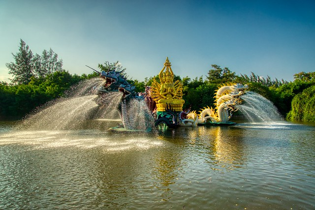 Sculpture with fountains in a lake in the evening sun in Muang Boran (Ancient City) in Samut Phrakan near Bangkok, Thailand