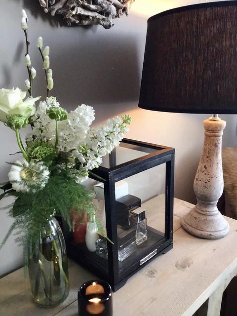 Zwart glazen box met parfumflesjes balusterlamp fles met witte bloemen