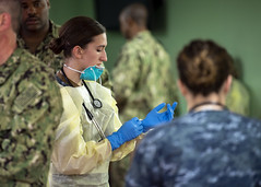 Hospital Corpsman 3rd Class Kimberly Wyss dons surgical gloves aboard USNS Mercy (T-AH 19), March 29. (U.S. Navy/MC2 Ryan M. Breeden)