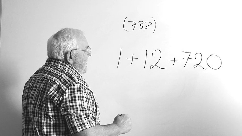 Teacher standing in front of a white board writing a mathematical equation