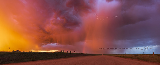 Sunset thunderstorm with rainbow and lightning.
