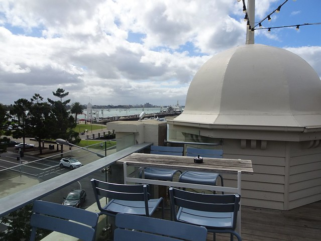 Geelong. A city of cuploas. The 1912 built small cupola on the roof of the Sailors Rest Building on the waterfront. Beyond the pier are the industrial buildings of North Geelong. Side view says King Edward 7 Sailors Rest home.