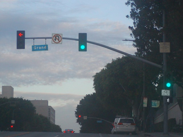 Westbound 1st Street - Tom Bradley Boulevard approaches, proceeds and crosses to turn left at Grand Avenue intersection traffic signal green lights, left turn protected red yellow green arrow lights flashing red lights (No U Turn signages)