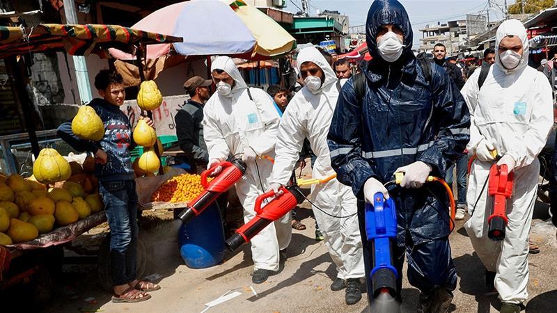 防疫人員於加薩市場進行消毒。(圖片來源:Adel Hana/AP Photo)