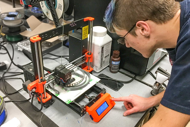 A 3D printer is adjusted by a technician at Somerset Community College