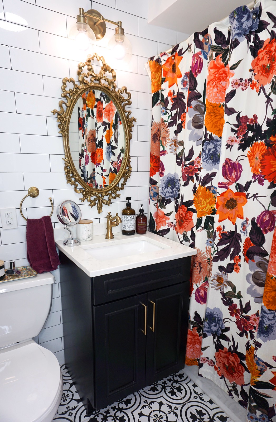 White Subway Tiled Bathroom | Vintage Antique Bathroom Style | Gold Hardware Accents | Black White Tile Bathroom Floor | Anthropologie Floral Shower Curtain | Black Bathroom Vanity Cabinet