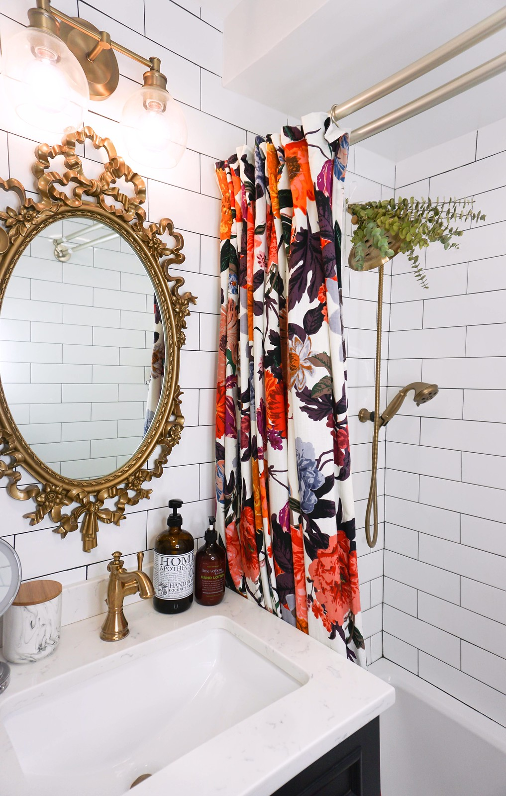 Eclectic Boho Colorful Small Bathroom | Gold Antique Mirror and Fixtures | Bold Floral Shower Curtain | Floor to Ceiling White Subway Tile | Eucalyptus Shower Head