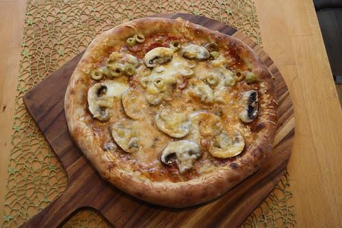 Große Pizza zum Teilen (eine Hälfte nur mit Champignons, die andere Hälfte mit frischen Champigons, scharfer Salami und grünen Oliven)