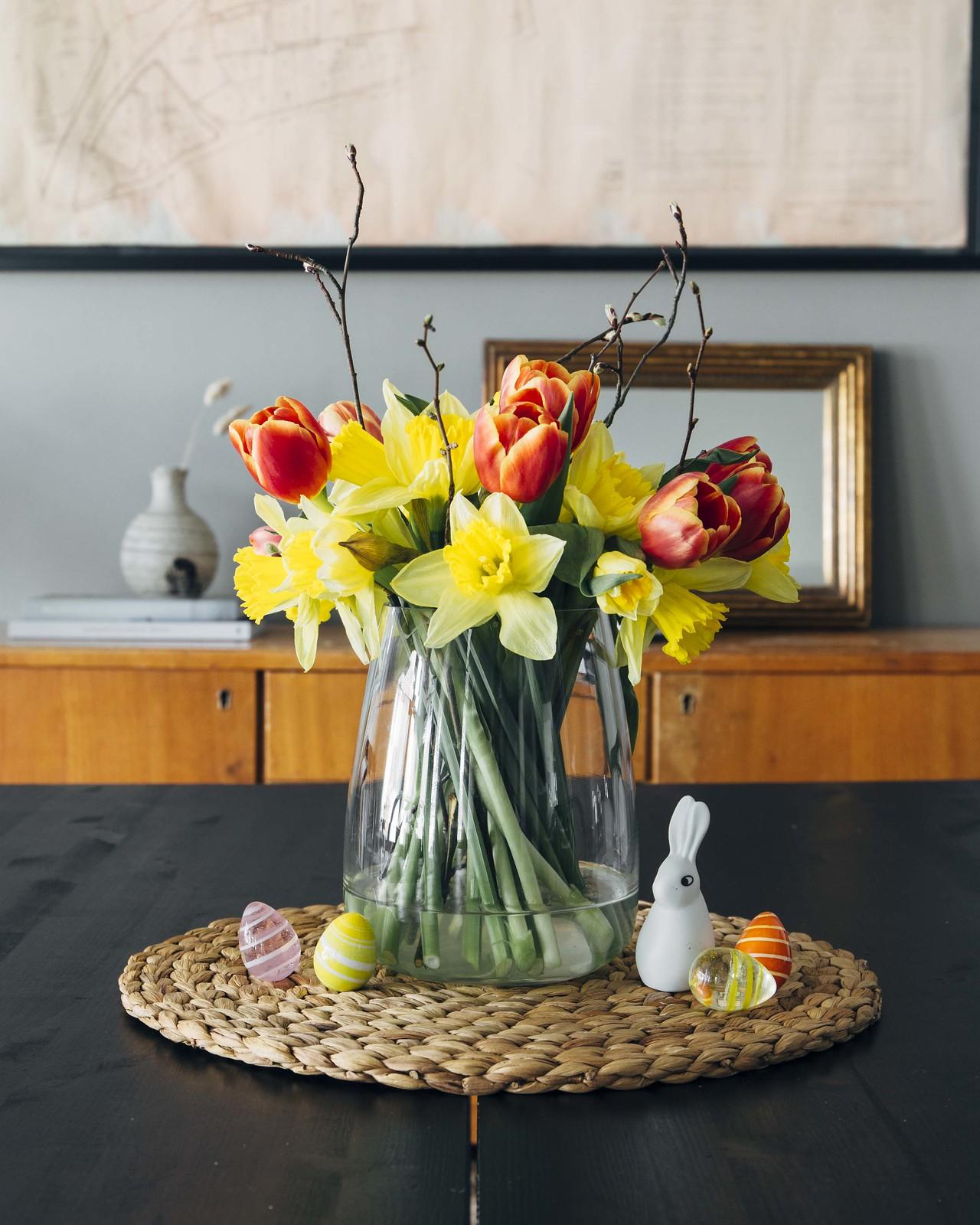Värikäs kukkakimppu, jossa on punaisia tulppaaneja, keltanarsisseja ja oksia, sopii täydellisesti pääsiäiseen.