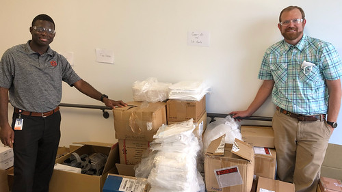 Emmanuel Winful and Christian Brodbeck stand among boxes of medical supplies