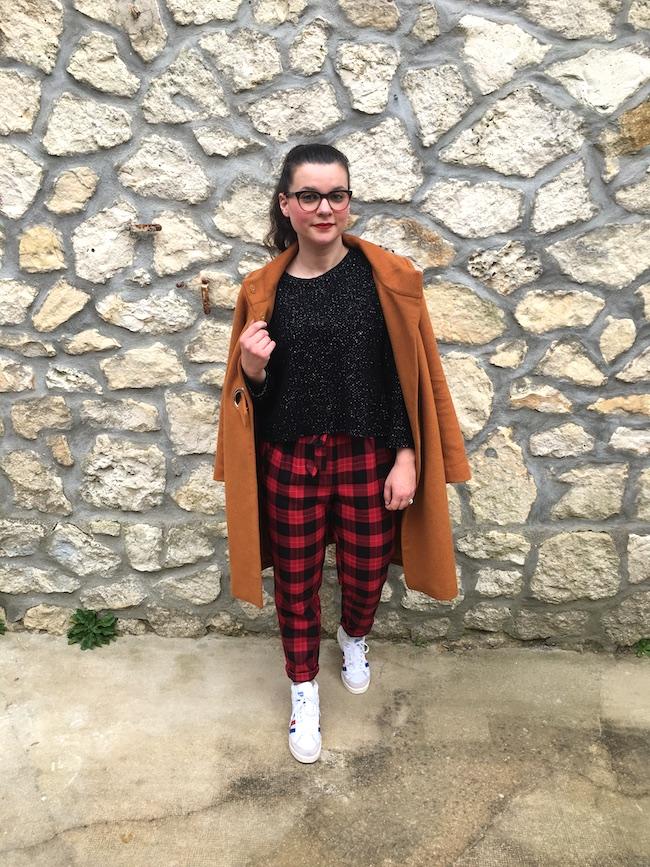 Look en manteau marron, pull à paillettes, pantalon tartan et baskets adidas