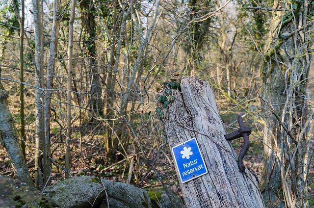 Skylt med naturreservat på gammal grindstolpe