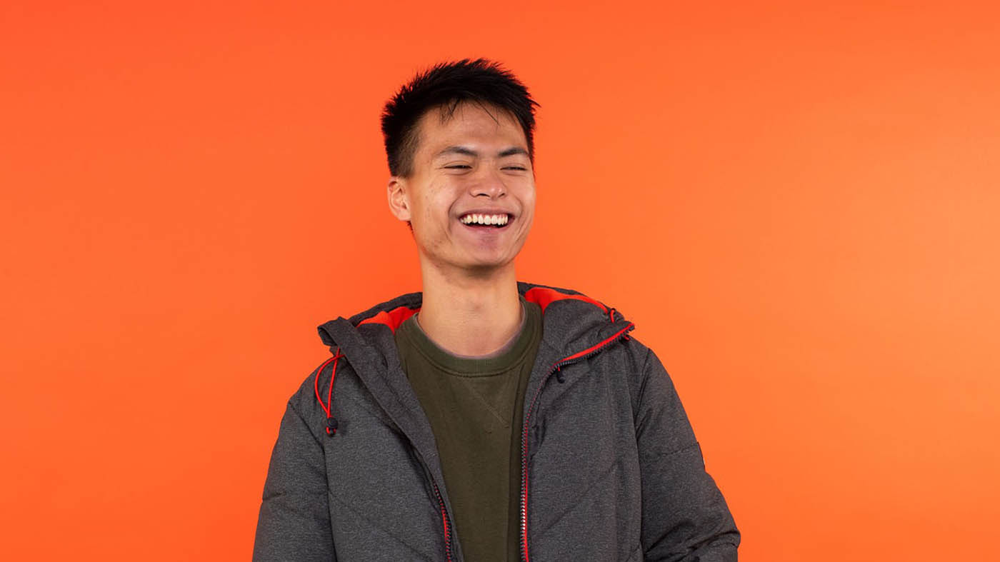 Godfrey laughs, looking slightly away from the camera, against an orange backdrop